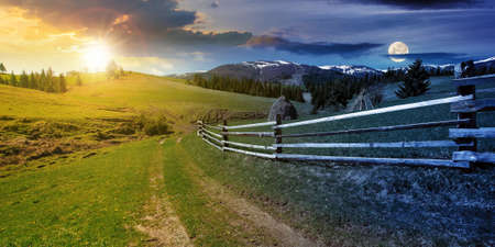 day and night time change concept above rural landscape in spring. path through grassy field. wooden fence on rolling hills. snow capped ridge in the distance. wonderful countryside scenery with sun and moon