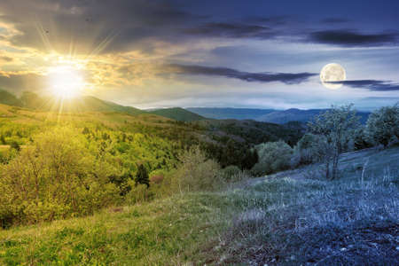 day and night equinox time change concept above mountainous countryside scenery in spring. trees and grass on hills rolling through green valley in to the distant ridge with sun and moon on the sky Banque d'images