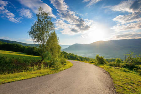countryside road in mountains on a sunny day. beautiful view in to the distant foggy valley from the top of the pass. trees along the way. wonderful rural landscape in summer