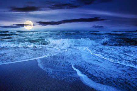 sea tide on a cloudy sunrise. green waves crashing golden sandy beach in full moon light. storm weather approaching. summer holiday concept Archivio Fotografico