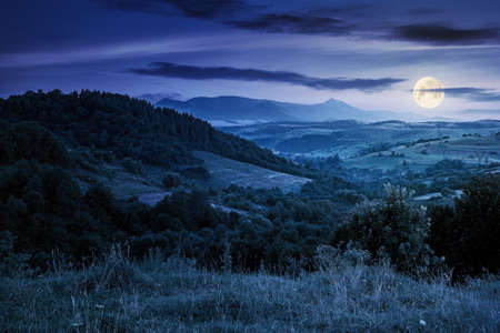 mountainous rural landscape at night. beautiful scenery with forests, hills and meadows in full moon light. ridge with high peak in the distance. village in the distant valley