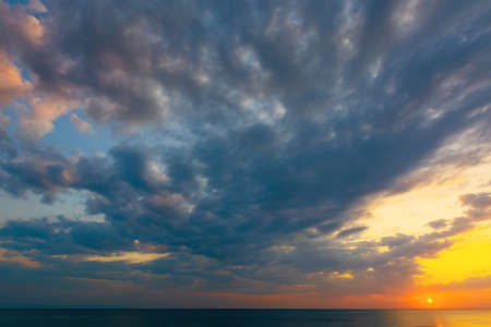 dynamic cloudscape in summer at sunrise. dark clouds on the sky in yellow and pink morning light. dramatic weather condition, picturesque scenery above the sea