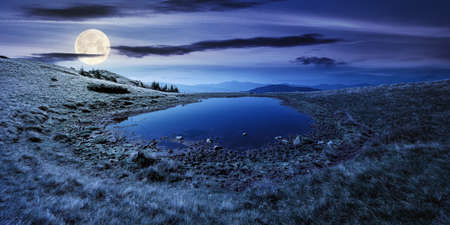 pond on the mountain meadow at night. wonderful summer landscape in full moon light. grass and trees on the hills. ridge in the distance. beautiful wide panorama Stock Photo