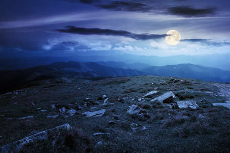 carpathian summer mountain landscape at night. beautiful countryside with rocks on the grassy hill in full moon light clouds on the blue sky. wonderful travel destination