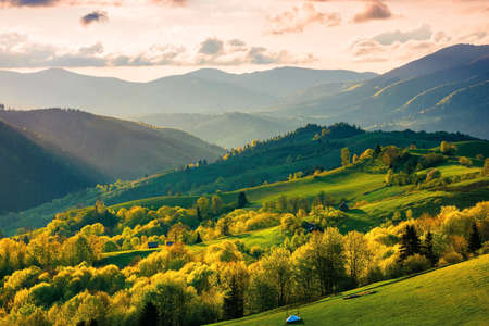 rural landscape in mountains at sunset. dramatic weather above the distant valley in springtime. green fields and trees on the hill. beautiful nature scenery with clouds on the sky Stock Photo
