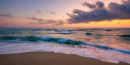 ocean beach with dramatic sky at sunrise. gorgeous vacation scenery. waves rolling on the sand in morning light Stock Photo