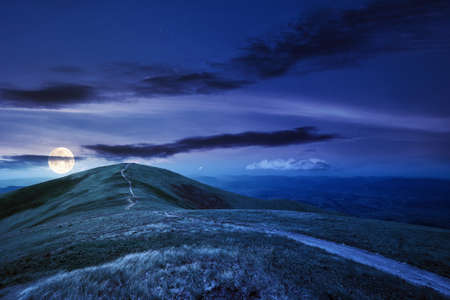 mountain landscape at night in spring. path through meadow in grass on the hill in full moon light. wonderful weather with fluffy clouds on the sky. borzhava ridge of carpathians