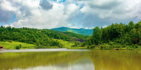 lake among mountain landscape in spring. beautiful countryside scenery with forest on the shore. clouds on the sky Stock Photo