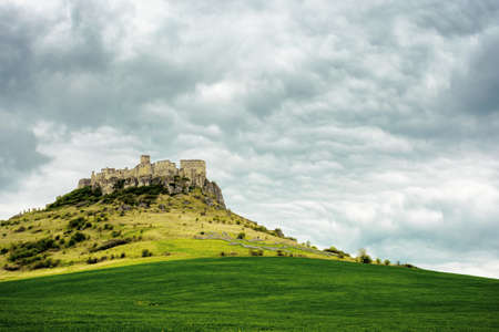 spis, slovakia - 29 APR 2019: castle ruins on the hill. grassy meadow in the foreground. popular travel destination on a cloudy day Editorial