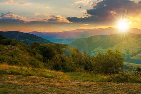 mountainous rural landscape at sunset. grassy meadow on top of a hill. clouds above the ridge in evening light. view in to the distant valley Stock Photo