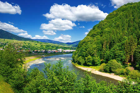 river runs through mountain valley. beautiful summer countryside landscape. village in the distance. wonderful scenery view. fluffy clouds on the deep blue sky