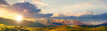 mountainous rural panorama landscape in springtime at sunset. beautiful scenery beneath a sky with clouds in evening light. grass covered hill rolling in to the distant ridge Stock Photo