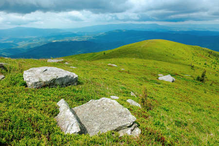 rock among the grass on the mountain meadow. beautiful green nature scenery in summer. view in to the distant valley. clouds above the highland ridge