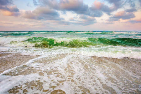 sea tide on a cloudy sunset. green waves crashing golden sandy beach. storm weather approaching. summer holiday concept Stock Photo