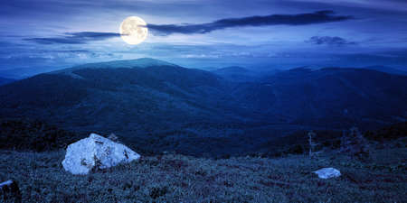 carpathian summer mountain landscape at night. beautiful countryside with rock on the grassy hill. view in to the distant valley in full moon light. clouds on the blue sky
