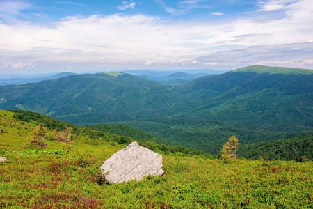 carpathian summer mountain landscape. beautiful countryside with rock on the grassy hill. view in to the distant valley. clouds on the blue sky