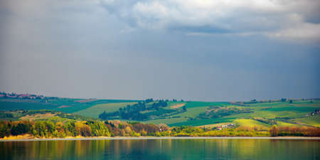 liptovska mara lake of slovakia. beautiful landscape in spring. reflection on the water surface. distant mountains in clouds Stock Photo
