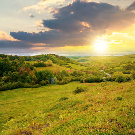 carpathian countryside in spring at sunset. beautiful rural landscape in mountain. wet grassy meadow in evening light. road winding through valley to village. distant ridge in the clouds