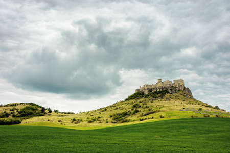 spis, slovakia - 29 APR 2019: castle ruins on the hill. grassy meadow in the foreground. popular travel destination on a cloudy day Stock Photo