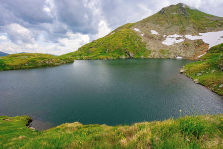 summer scenery with lake on high altitude. beautiful landscape of fagaras mountain ridge in summer. open view in to the distant peak beneath a fluffy clouds Stock Photo