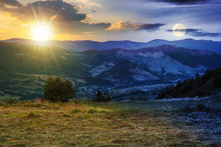 day and night time change above the mountainous rural landscape. grassy meadow on top of a hill. clouds above the ridge with sun and moon. view in to the distant valley at twilight