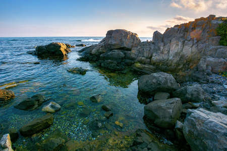 sea coast scenery in the morning. boulders in the calm water. few clouds on the sky in forenoon light. lonely place for summer vacations. sunny weather