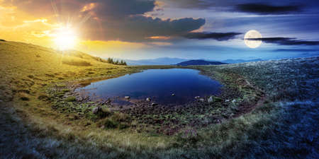 day and night time change concept above pond on the mountain meadow. wonderful summer landscape with sun and moon. grass and trees on the hills. ridge in the distance. beautiful wide panorama Stock Photo