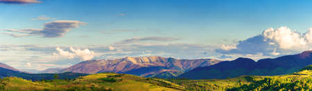 mountainous rural panorama landscape in springtime. beautiful scenery beneath a sky with clouds. grass covered hill rolling in to the distant ridge Stock Photo