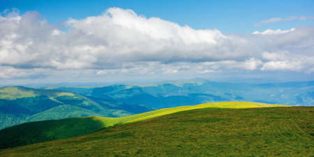 nature landscape of carpathian mountains. beautiful rolling scenery with grassy meadows in summer. clouds on the sky above the distant watershed ridge Stock Photo