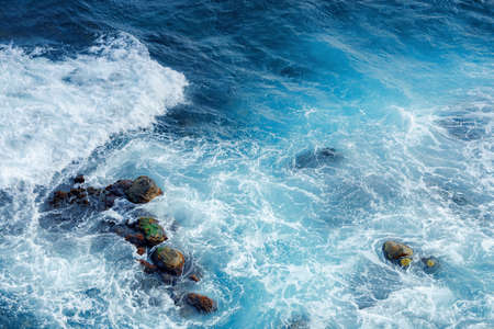 crushing sea waves texture. beautiful nature background view from above. unbelievable blue color of water. few rocks among foam