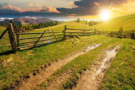 mountainous rural landscape at sunset in spring. path through grassy field. wooden fence on rolling hills. snow capped ridge in the distance. wonderful countryside scenery in evening light Stock Photo