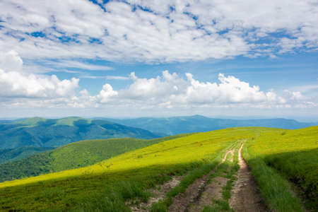 wide trail through grassy meadow. mountain ridge in the distance beneath a gorgeous cloudscape on the blue sky. travel backcountry concept Stock Photo