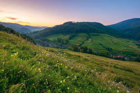 rural valley landscape at dawn. beautiful carpathian nature scenery with grassy hills, fields and meadows between forested hills. small village in the distance. cloudless sky Stock Photo
