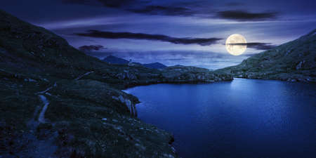 summer landscape with lake on high altitude at night. beautiful scenery of fagaras mountain ridge in summer. open view in to the distant peak beneath a fluffy clouds in full moon light