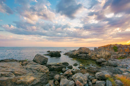 summer vacation scenery by the sea at sunrise. calm water washes pebble beach with stones and boulders. dramatic clouds above horizon in morning light on the sky Stock Photo