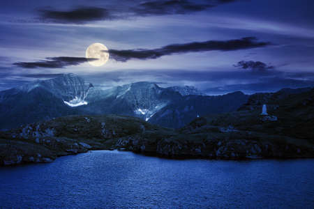summer scenery with lake on high altitude at night. beautiful landscape of fagaras mountain ridge in summer. open view in to the distant peak beneath a fluffy clouds in full moon light Stock Photo