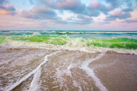 cloudy seascape scenery in evening light. waves crush on the sandy beach. dramatic weather nature background