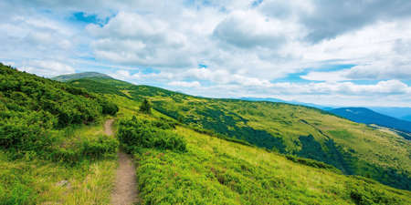 trail uphill the alpine meadow to the distant summit. beautiful mountain landscape in summertime. clouds on the sky. travel countryside concept