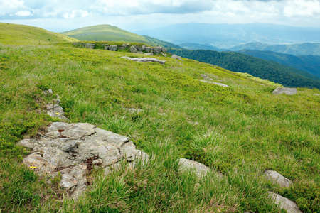 stones on the hill of mountain meadow. beautiful summer landscape with clouds above the horizon Stock Photo