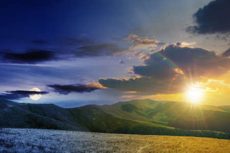 day and night time change concept above mountain landscape in summer. grassy meadows on the hills rolling in to the distant peak beneath sky with sun and moon Stock Photo