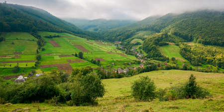 village in the valley of carpathian mountains. rural landscape in early autumn. fields and pastures on the hillside meadows. wonderful nature scenery in the morning