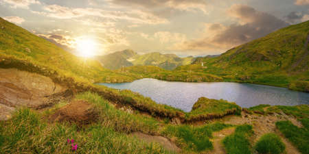 summer landscape with lake on high altitude at sunset. beautiful scenery of fagaras mountain ridge in summer. open view in to the distant peak beneath a fluffy clouds in evening light Stock Photo