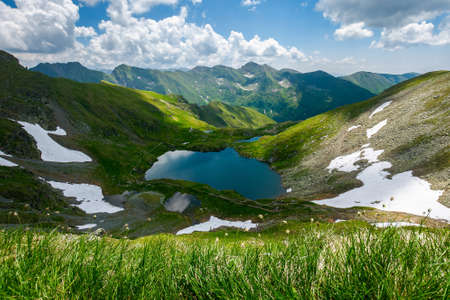 capra lake of fagaras mountains. wonderful summer nature scenery on a sunny day. popular travel destination of romania. snow and grass on the slopes. fluffy clouds on the sky Stock Photo