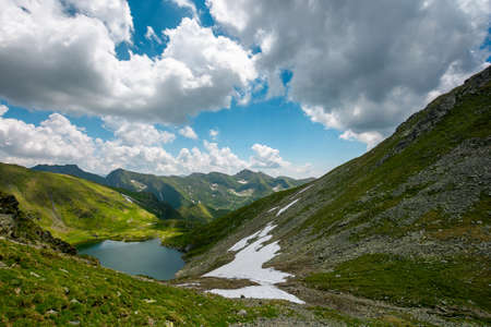 mountain summer landscape with alpine lake. beautiful nature scenery of fagaras mountain ridge, romania. sunny weather with fluffy clouds on the sky. popular travel destination