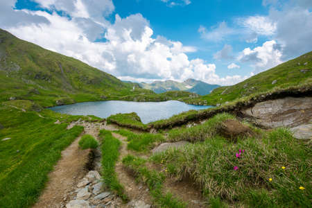 landscape with lake in mountains. wonderful summer nature scenery on a cloudy day. popular travel destination of fagaras ridge, romania. grass and stones on the slopes. dramatic clouds on the sky Stock Photo