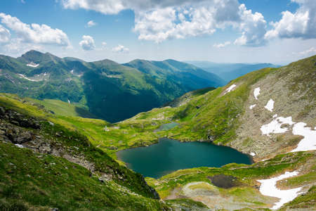 capra lake of fagaras mountains. wonderful summer nature scenery on a sunny day. popular travel destination of romania. snow and grass on the slopes. fluffy clouds on the sky Banque d'images