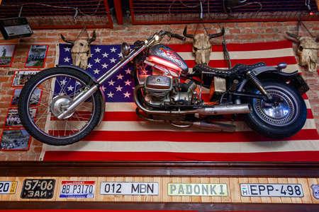 Uzhhorod, ukraine - NOV 22, 2008: interior of bikers bar. motorbike and us flag on the wall
