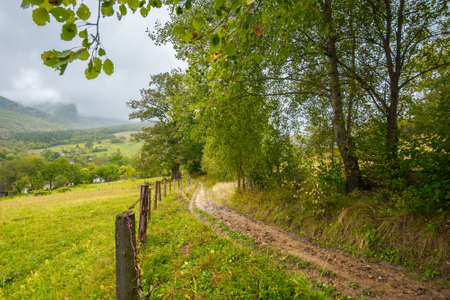 rural dirt road to village. autumnal countryside of carpathian mountains. rainy weather. fence along the meadow. gray heavy clouds above the valley