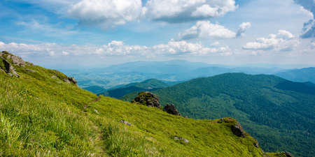 view from pikui mountain. huge stones on the grassy slopes. summer landscape of carpathian mountains. borzhava ridge in the distancee beneath a sky with clouds Stock Photo