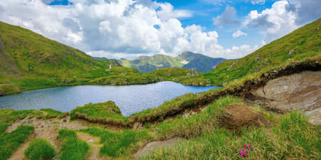 summer landscape with lake on high altitude. beautiful scenery of fagaras mountain ridge in summer. open view in to the distant peak beneath a fluffy clouds. Capra lacul, Romania